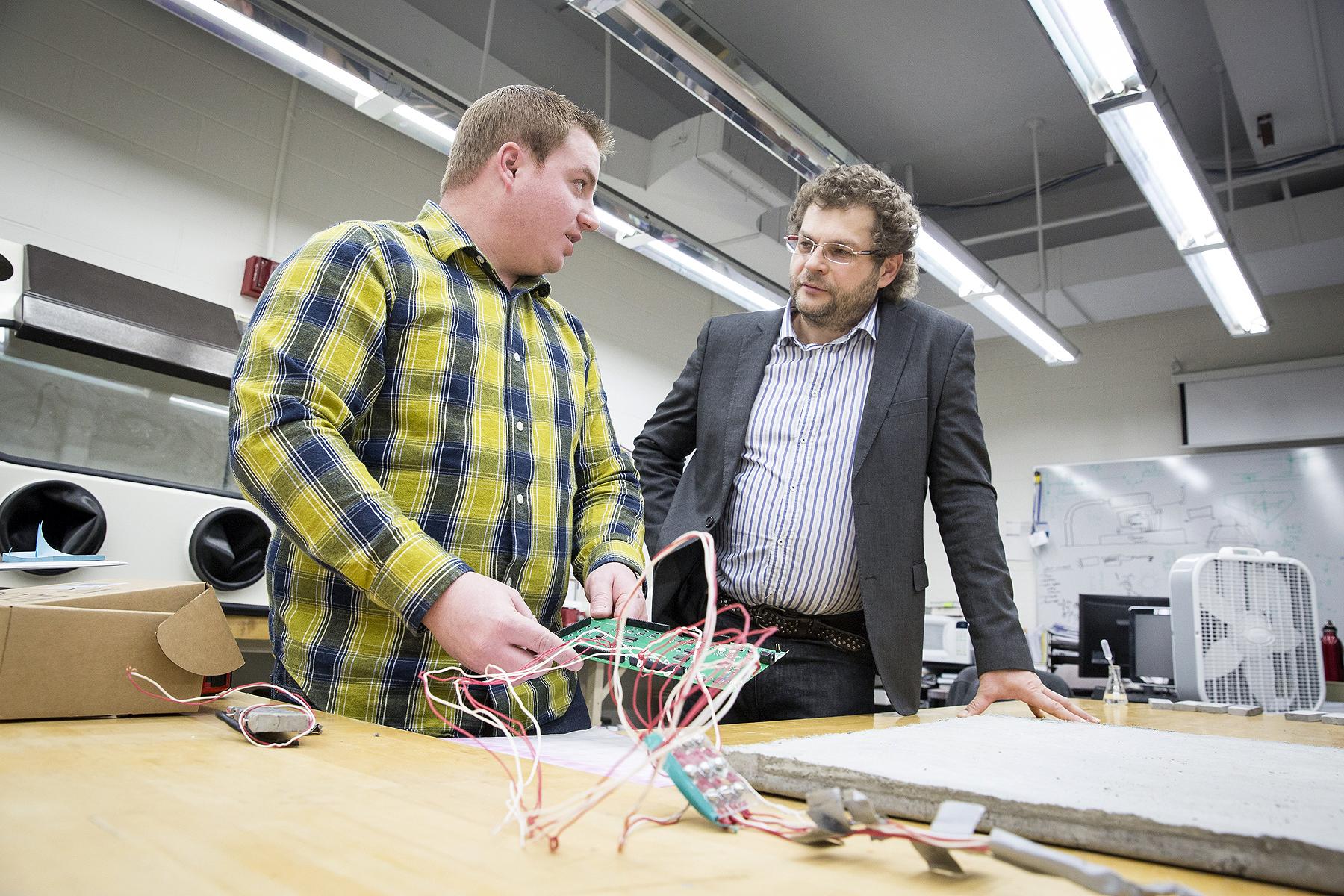 Pesquisador Konstantin Sobolev (dir.) e estudante de doutorado Scott Muzenski, ambos da UWM, testam placa do concreto que repele água