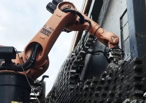 Braço mecânico atua com precisão milimétrica, assentando os tijolos e injetando argamassa
