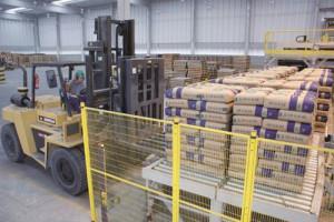 Paletizadora na Cia. de Cimento Itambé entrega o volume correto de sacos de cimento, para que a empilhadeira possa carregar os paletes nos caminhões. Crédito: Cia. de Cimento Itambé